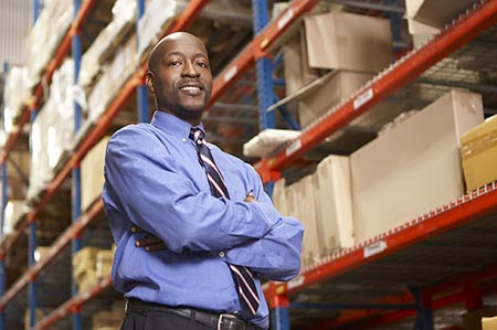 Man in warehouse where thermal fluid heater spare parts are stocked